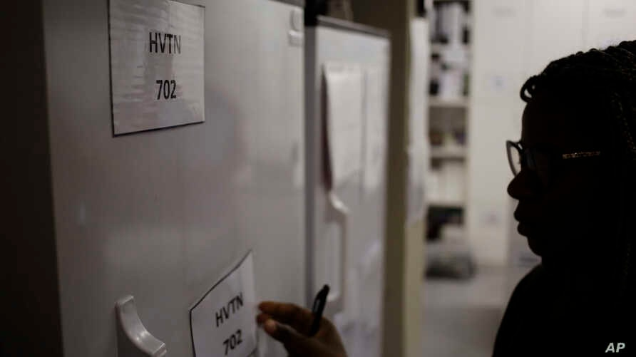 Pharmacist Mary Chindanyika labels a fridge containing a trial vaccine against HIV on the outskirts of Cape Town, South Africa, Nov. 30, 2016. The latest attempt in the long, frustrating search for a vaccine against HIV has begun in South Africa.