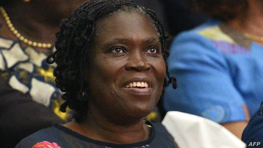Simone Gbagbo, Ivory Coast's former first lady, smiles as she sits in the dock at the Court of Justice in Abidjan on Dec. 26, 2014 for the start of her trial.