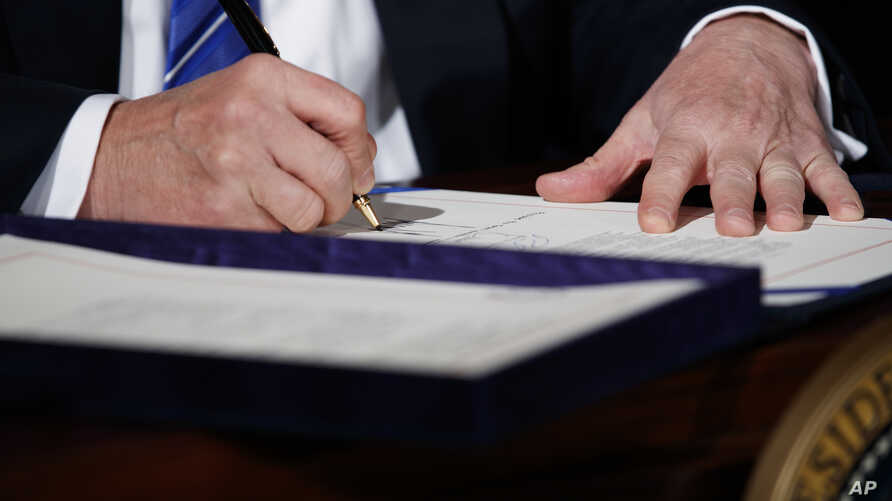 "President Donald Trump signs the ""Department of Veterans Affairs Accountability and Whistleblower Protection Act of 2017"" in the East Room of the White House, June 23, 2017, in Washington."