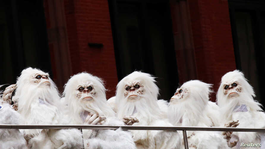 FILE - Actors dressed as a yeti ride a tour bus in Manhattan, New York City, Oct. 4, 2016.