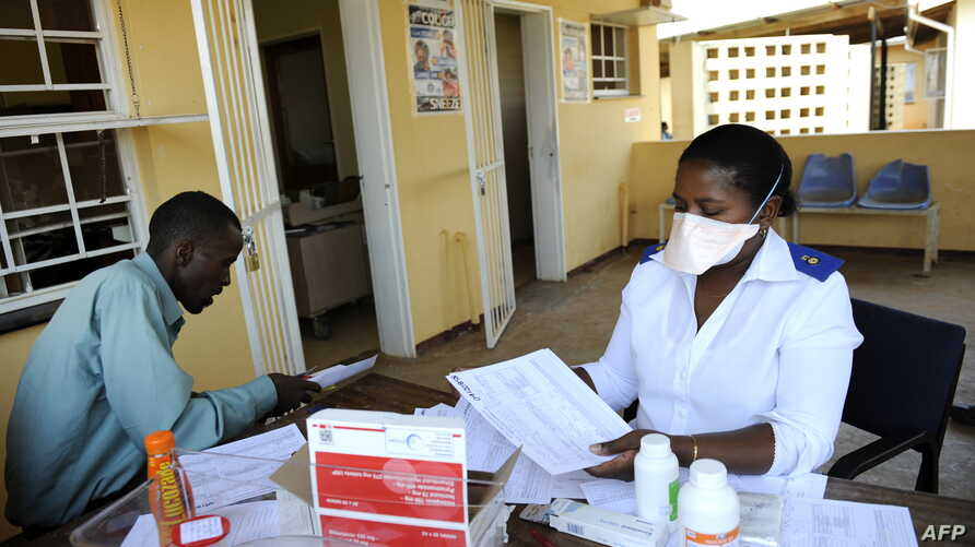 A patient waits for his pills as he meets with a nurse at Nhlangano health center in Swaziland, Oct. 28, 2009.