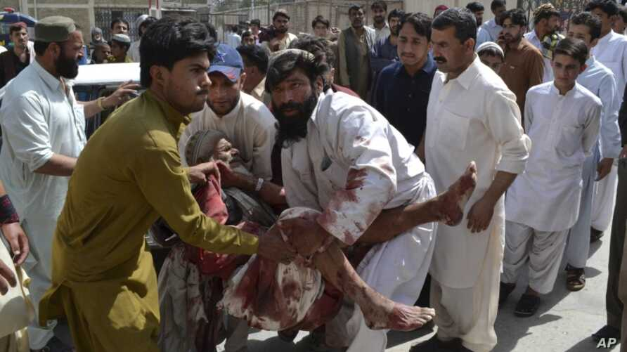 People rush an injured man to hospital following a bomb blast near a rally by the Awami National Party that killed at least five people, in Quetta, Pakistan, Friday, July 13, 2012.