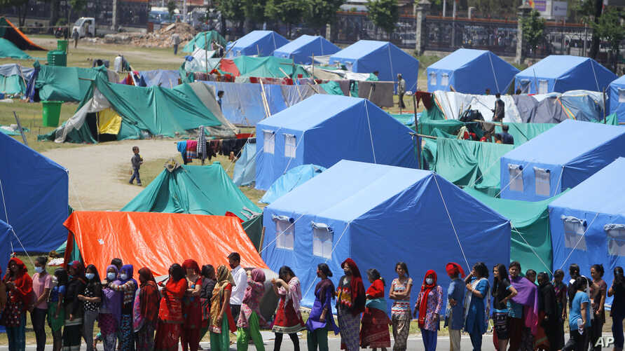 People who have had their homes damaged and are living in tents during the April 25 earthquake line up for drinking water and packaged noodles in Kathmandu, Nepal, May 3, 2015.
