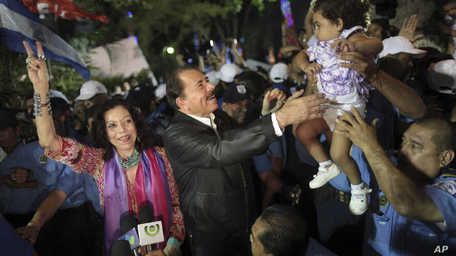 FILE.- In this Nov. 8, 2011 file photo Nicaragua's President Daniel Ortega, center, accompanied by his wife Rosario Murillo, left, greets supporters after delivering an address to the nation in Revolution Square in Managua, Nicaragua. First lady Rosa