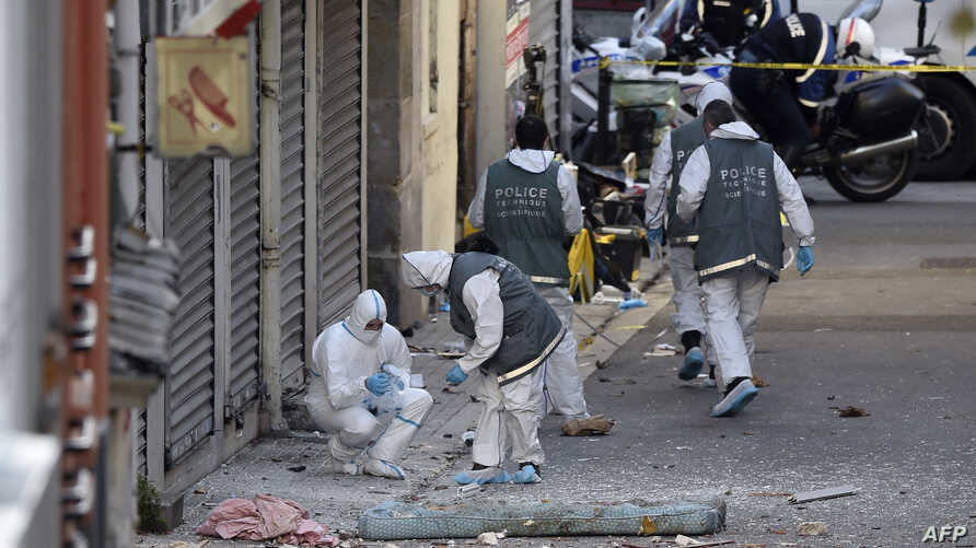 French forensics police search for evidence outside a building in Saint-Denis, where special forces raided an appartment, hunting those behind the attacks that claimed 129 lives in Paris last week, Nov. 18, 2015.