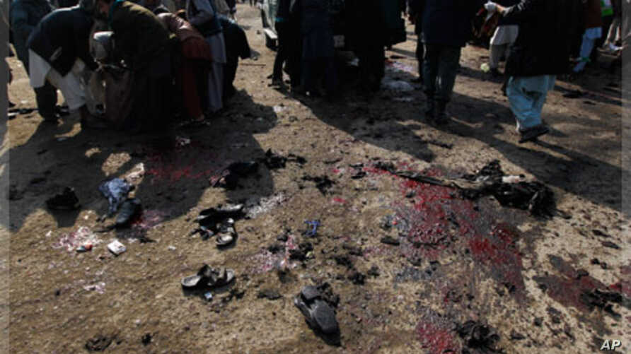 People help clear casualties from the site of a suicide attack at a Shi'ite Muslim gathering in Kabul, December 6, 2011.