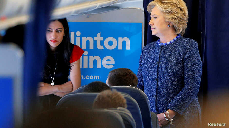 U.S. Democratic presidential nominee Hillary Clinton talks to staff members, including aide Huma Abedin (L), onboard her campaign plane in White Plains, New York, U.S. Oct. 28, 2016.