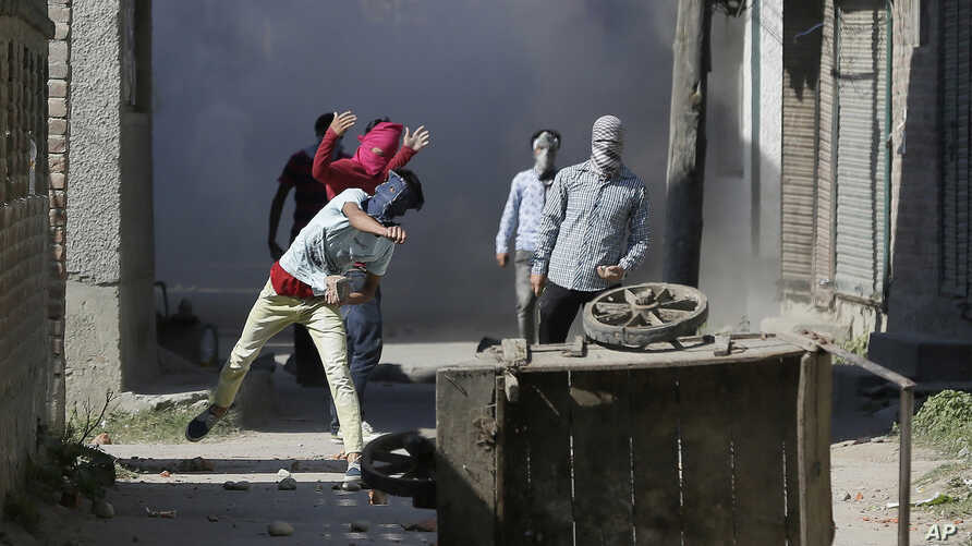 Kashmiri Muslim protesters throw stones at government forces in Srinagar, Indian controlled Kashmir, Sept. 23, 2016.