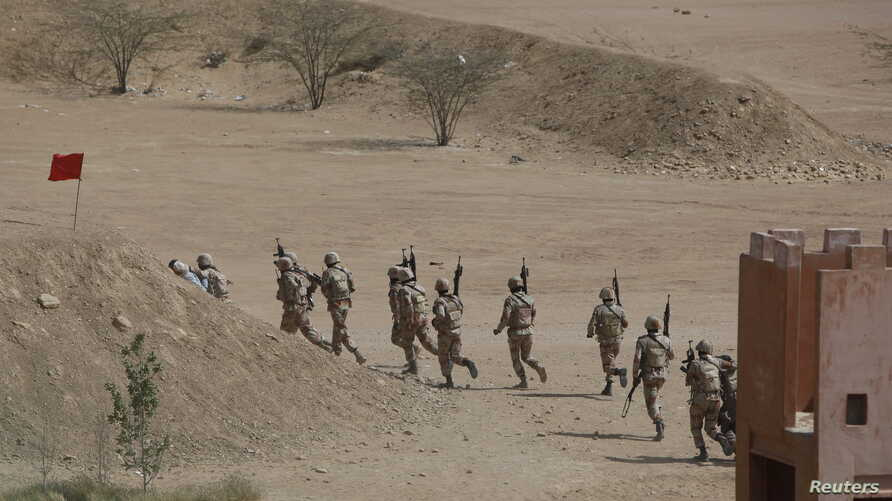 FILE - Pakistan Rangers walk with their weapons during a counter-terrorism training demonstration on the outskirts of Karachi, Pakistan, Feb. 24, 2015.