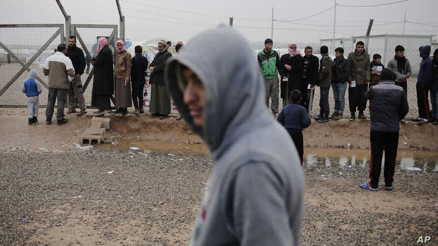 Displaced people wait for aid at a camp east of Mosul, Iraq, Feb. 15, 2017. The United Nations says they are temporarily pausing aid operations to neighborhoods in eastern Mosul retaken from the Islamic State group for security reasons.