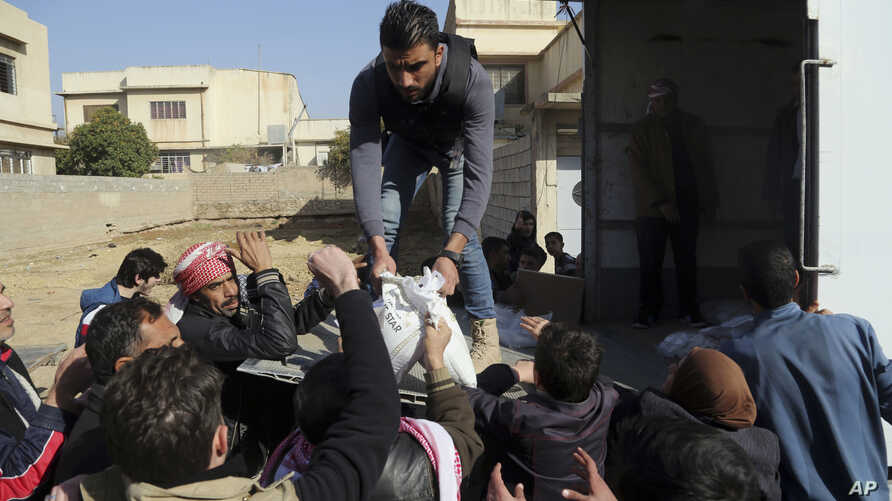 Residents of a neighborhood recently liberated from Islamic State militants gather for humanitarian aid in the eastern side of Mosul, Iraq, Jan. 11, 2017.