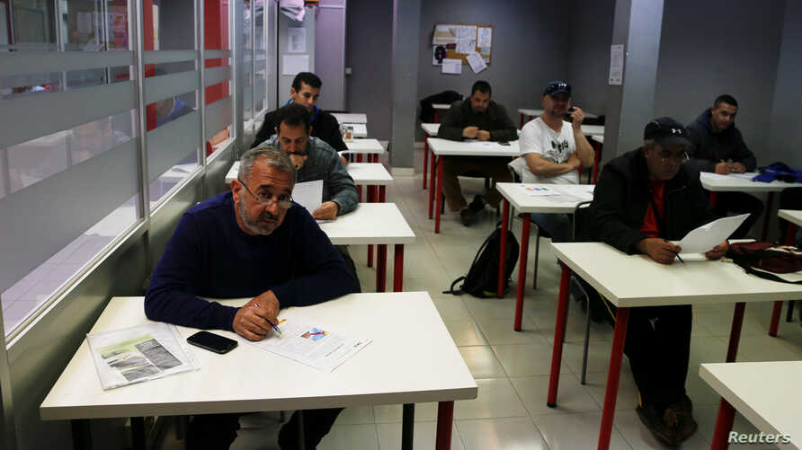 Osama Abdul Mohsen (L), a Syrian refugee, attends a Spanish lessons at a YMCA social center in Getafe, outside Madrid, Spain, April 21, 2016.