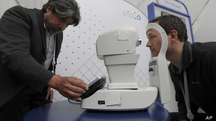 Jorge Cuadros, left, gives a demonstration of a robotic retinal camera to a reporter at the Google I/O conference in Mountain View, Calif., Tuesday, May 8, 2018.
