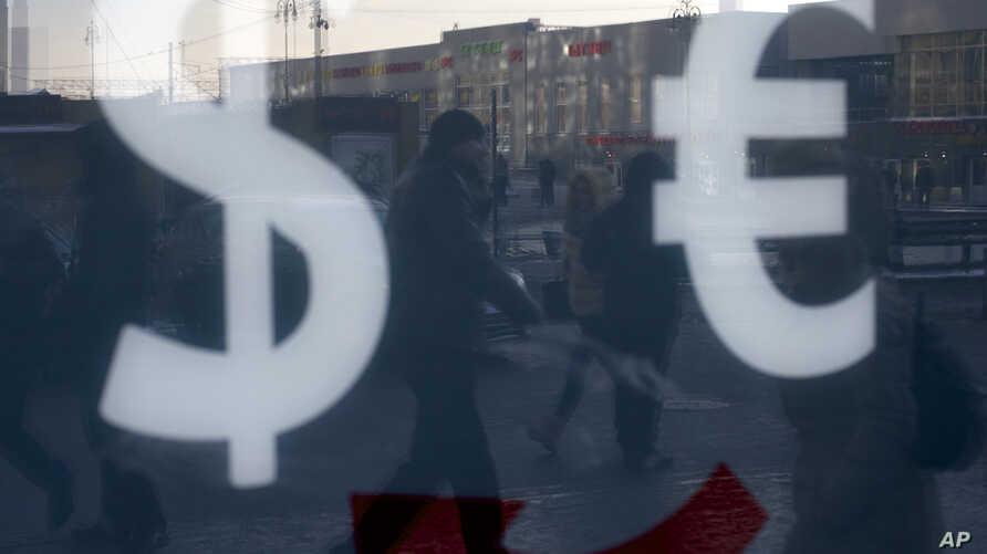 FILE - People walk along a street passing an exchange booth in downtown Moscow, Russia.