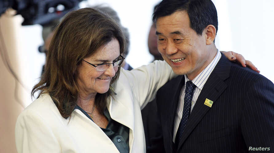 Maria das Gracas Silva Foster (L), CEO of Brazil's state oil company Petrobras, greets Bo Qiliang, President of CNODC, during a signing ceremony for the First Contract of Brazilian Pre-Salt, attended by Brazil President Dilma Rousseff, ministers and