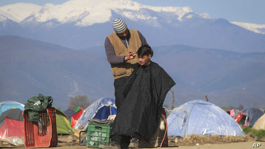 A man gets a haircut from a fellow migrant at the northern Greek border point of Idomeni, Greece, Sunday, March 20, 2016.
