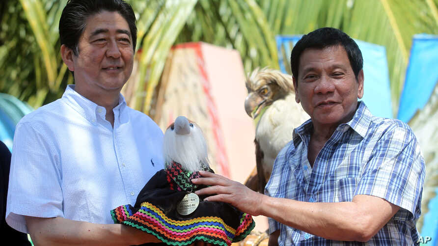 Philippine President Rodrigo Duterte, right, hands over a Philippine Eagle stuffed toy named Sakura to Japan's Prime Minister Shinzo Abe during the ceremonial eagle naming at the garden area of Waterfront Insular Hotel in Davao City, southern Philipp