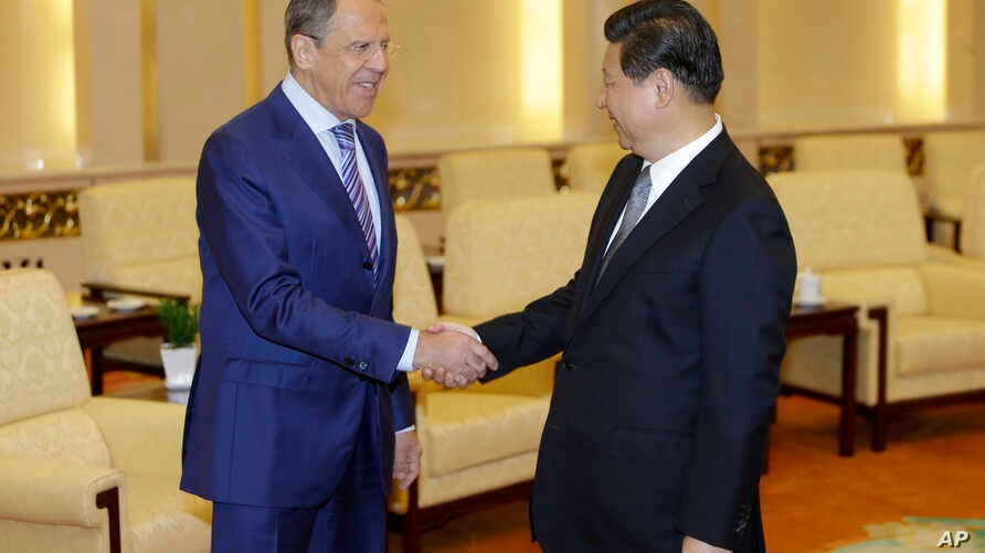 Russian Foreign Minister Sergei Lavrov (L), shakes hands with China's President Xi Jinping during a meeting at the Great Hall of the People in Beijing, Tuesday, April 15, 2014.