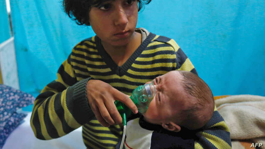 A Syrian boy holds an oxygen mask over the face of an infant at a makeshift hospital following a reported gas attack on the rebel-held besieged town of Douma in the eastern Ghouta region on the outskirts of the capital Damascus, Jan. 22, 2018.
