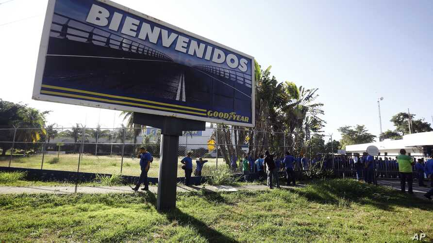 A Goodyear billboard emblazoned with the Spanish word for welcome, is posted near a plant entrance company where workers arrived to find the plant is no longer in operation, in Los Guayabos, Venezuela, Dec. 10, 2018.