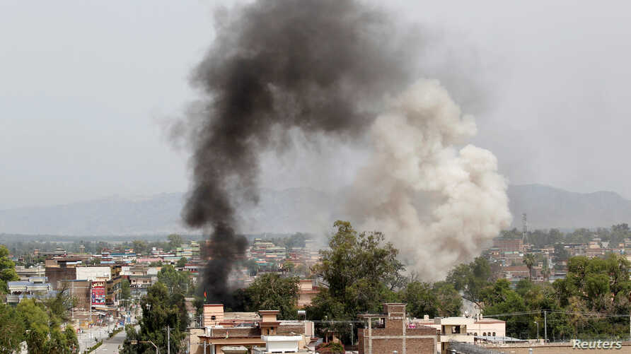 Smoke rises from the site of a blast and gunbattle between Afghan security forces and a handful of militants in Jalalabad city, Afghanistan, May 13, 2018.