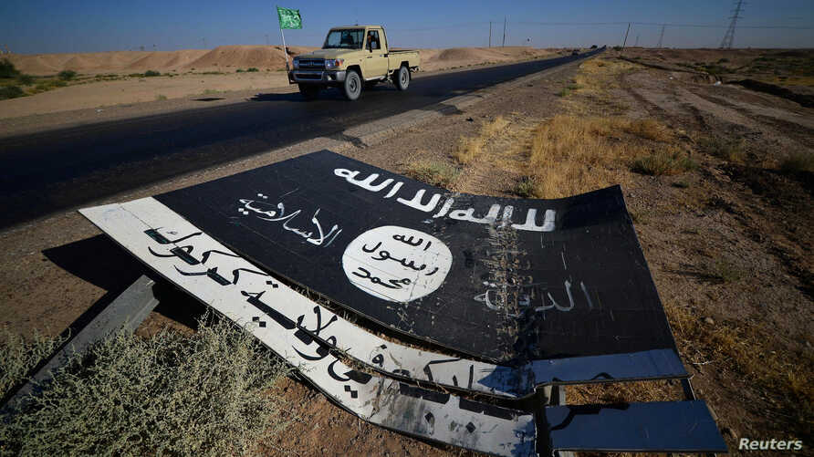 A black sign belonging to Islamic State militants is seen on the road in Al-Al-Fateha military airport south of Hawija, Iraq, Oct. 2, 2017.