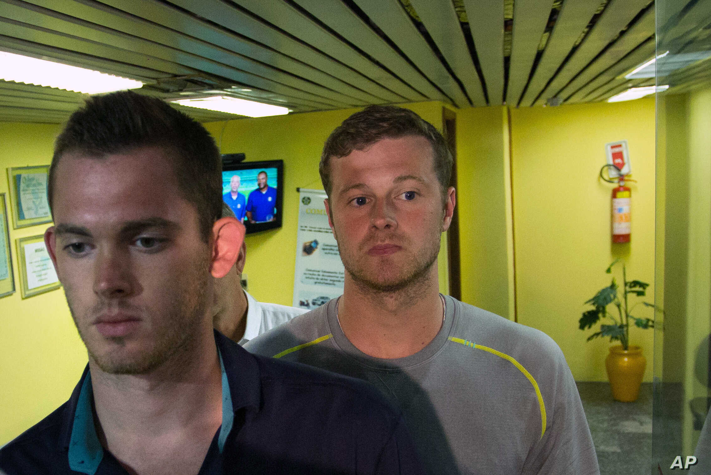 American Olympic swimmers Gunnar Bentz, left, and Jack Conger, center, leave the police station at Rio International airport early Thursday Aug. 18, 2016.