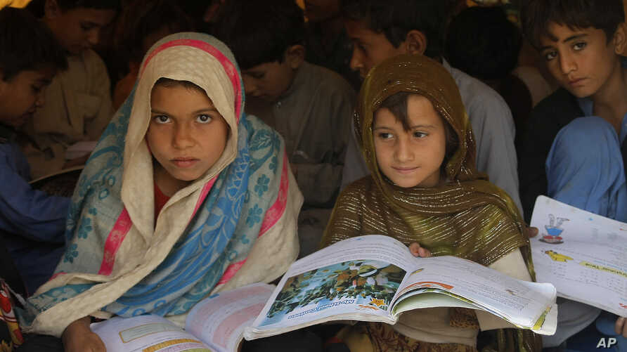 FILE - Pakistani children study in a makeshift school after fleeing from the neighboring Khyber tribal region due to fighting between security forces and militants, in Peshawar, Pakistan.