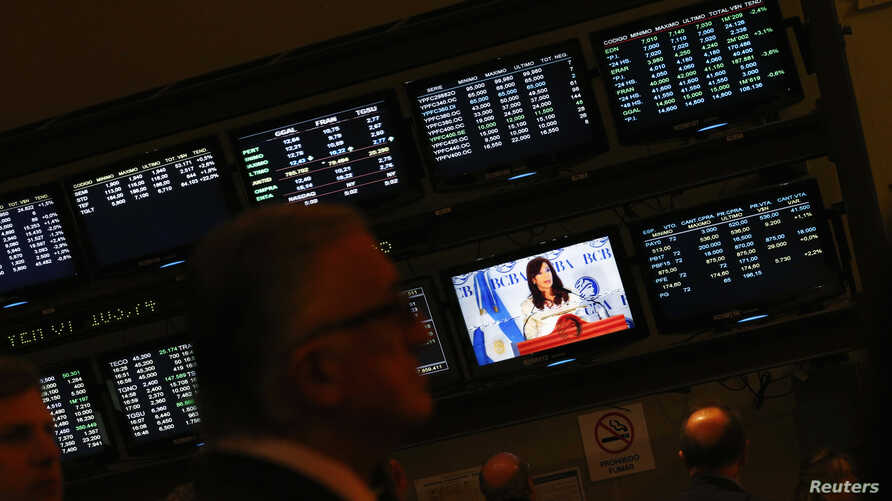 Attendants of a ceremony at Buenos Aires' Stock Exchange watch as Argentina's President Cristina Fernandez de Kirchner speaks, in Buenos Aires, Argentina, Aug. 20, 2014.