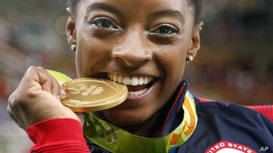 United States' Simone Biles bites her gold medal for the artistic gymnastics women's individual all-around final at the 2016 Summer Olympics in Rio de Janeiro, Brazil, Aug. 11, 2016.