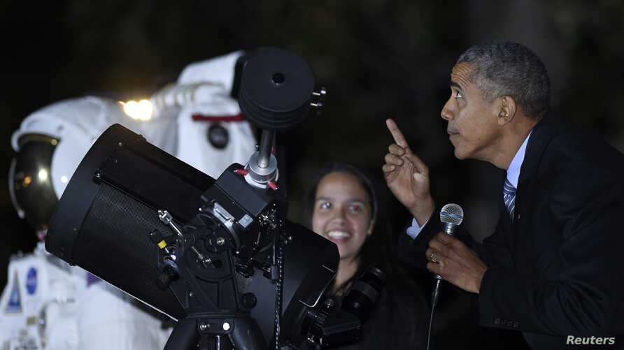 President Barack Obama looks up at the moon as he talks with Agatha Sofia Alvarez-Bareiro, left, a high school senior from the Brooklyn borough of New York, at the second-ever White House Astronomy Night on the South Lawn of the White House in Washin