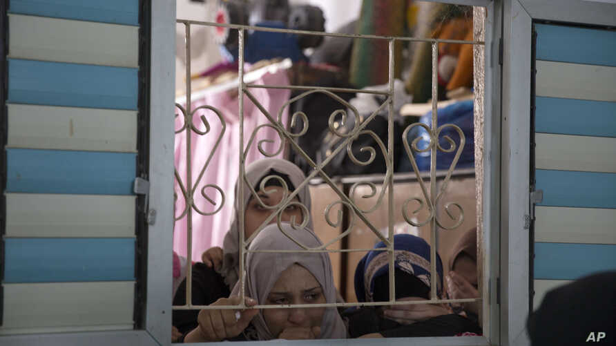 Palestinian relatives of Moaath al-Souri, who was shot and killed by Israeli troops on Friday's ongoing protest at the Gaza Strip's border with Israel, mourn at the family home during his funeral in Nuseirat refugee camp, central Gaza Strip, Saturday