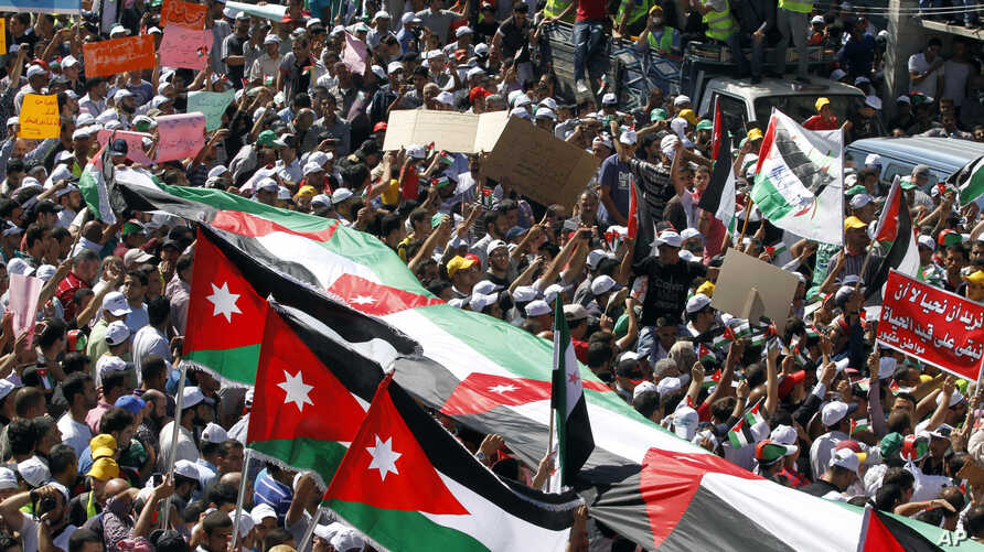 The Muslim Brotherhood's Islamic Action Front supporters carry banners and a large Jordanian at the biggest protest in the kingdom since late 2010, in Amman, Jordan, Friday, Oct. 5, 2012. (AP)