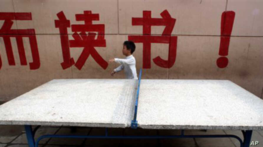 """A child walks past large Chinese characters which partly reads """"Study!"""" at the New Century Experimental School in Qikeshu village on the outskirts of Beijing (File Photo)"""