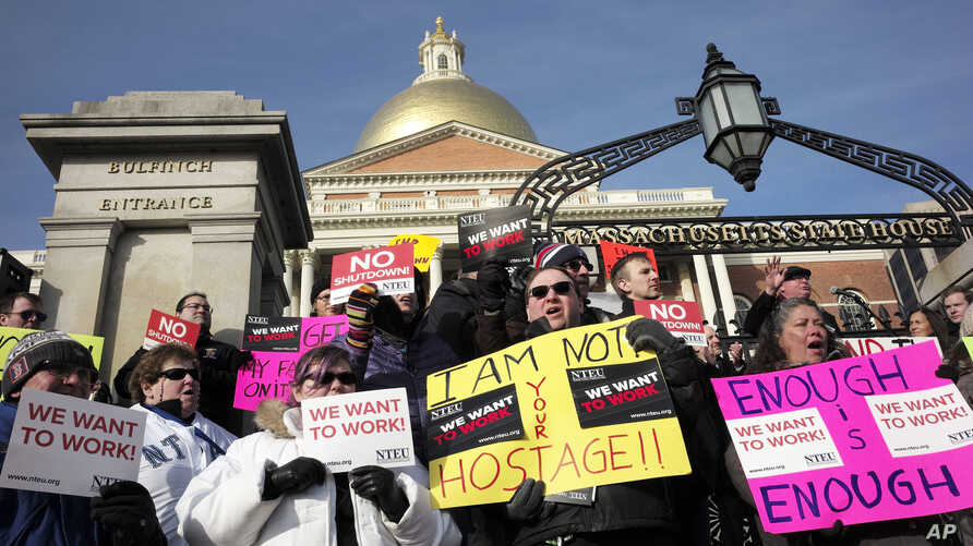 Internal Revenue Service employees Brian Lanouette, of Merrimack, N.H., center right, and Mary Maldonado, of Dracut, Mass., right, join with others as they display placards during a rally by federal employees and supporters, Jan. 17, 2019, in front o