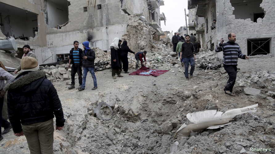 FILE - Residents inspect a crater at a site hit by what activists said were three consecutive air strikes carried out by the Russian air force, the last which hit an ambulance, in the rebel-controlled area of Maaret al-Numan town in Idlib province, S