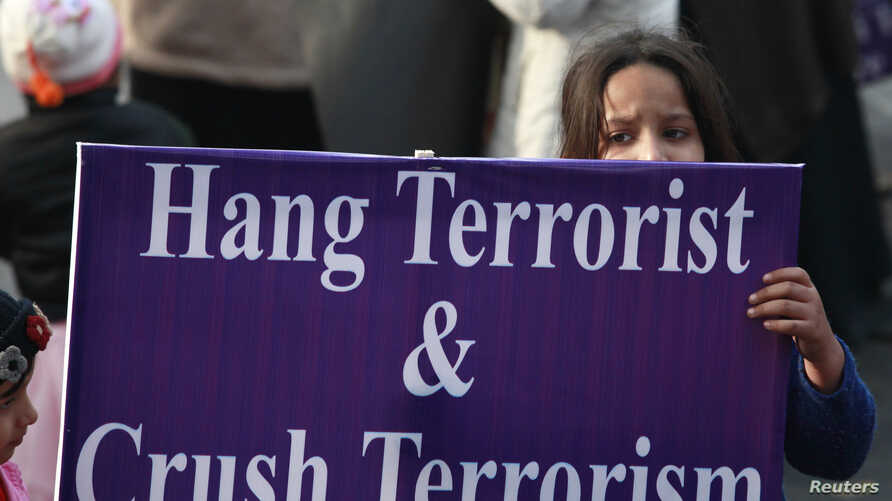 A child supporter of political party Pakistan Awami Tehreek (PAT), hold sign with others to condemn the attack by Taliban gunmen on the Army Public School in Peshawar, during a rally in Lahore, Dec. 21, 2014.