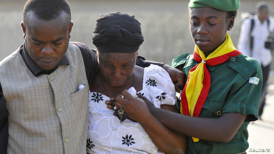 A woman is consoled by church members as she grieves near the graves of victims of a suicide bomb attack during a memorial service at St. Theresa's Church in Madalla, on the outskirts of Abuja, December 23, 2012.