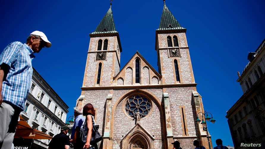 FILE - People walk past the Sacred Heart Cathedral in Sarajevo, Bosnia and Herzegovina, July 28, 2017.