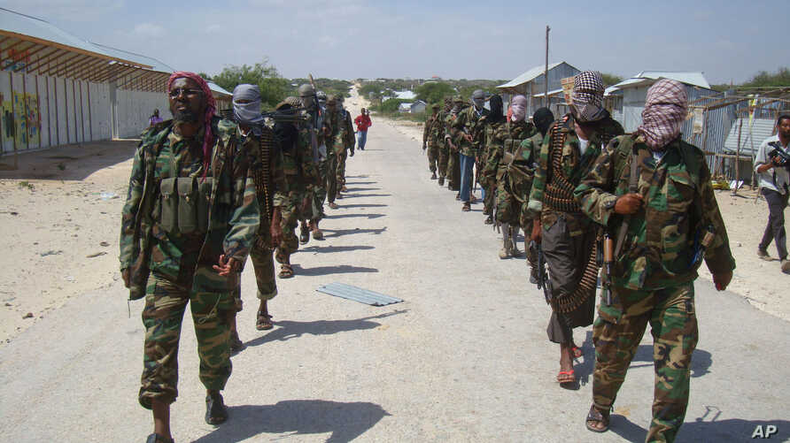 FILE - Members of Somalia's al- Shabab militant group march on the outskirts of Mogadishu, Somalia, March, 5, 2012.