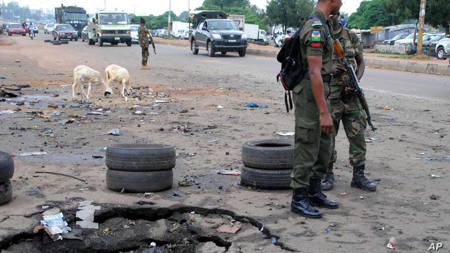 FILE - Police officers stand next to a checkpoint near the site of a Wednesday's blast in Kaduna, Nigeria, July 24, 2014.
