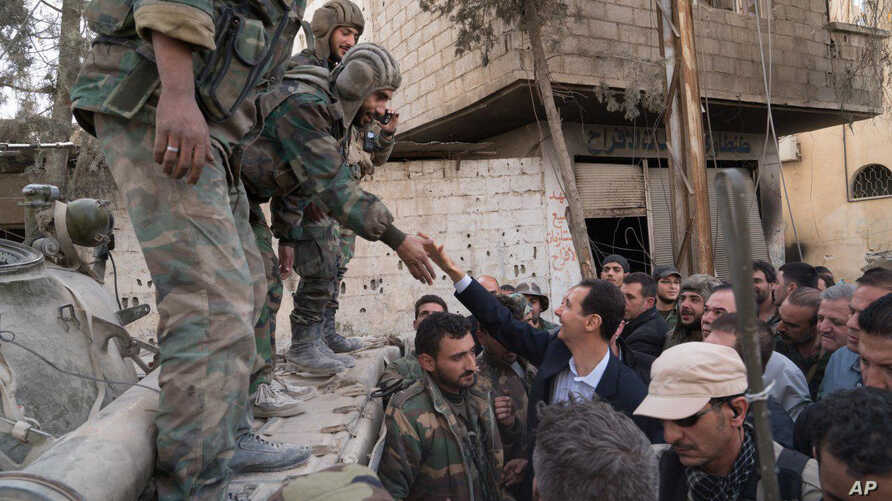 Syrian President Bashar al-Assad reaches out to shake the hand of a Syrian army soldier in eastern Ghouta, Syria, March 18, 2018.