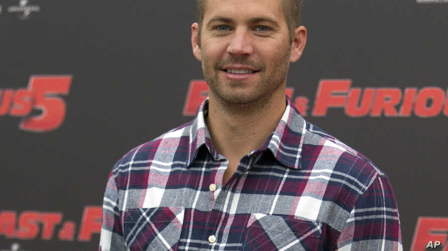 """FILE - In this April 29, 2011 file photo, actor Paul Walker poses during the photo call of the movie """"Fast and Furious 5,"""" in Rome."""