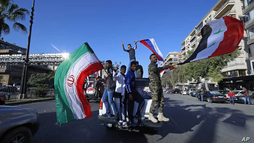 Hundreds of Syrians flash victory signs, honk car horns and wave Syrian, Iranian and Russian flags as they chant slogans against U.S. President Trump in Damascus, Syria, April 14, 2018.