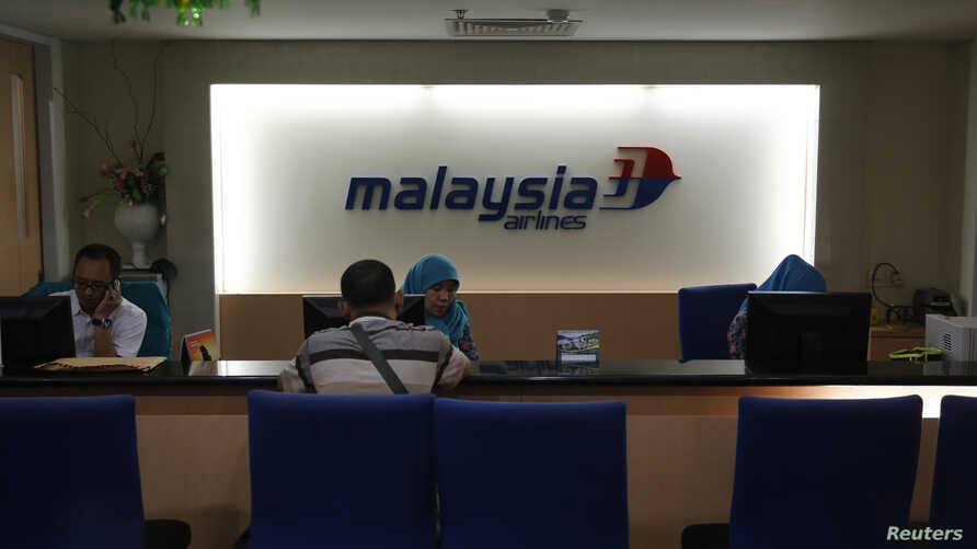 A Malaysia Airlines representative serves a customer at its ticket office in Jakarta July 18, 2014.