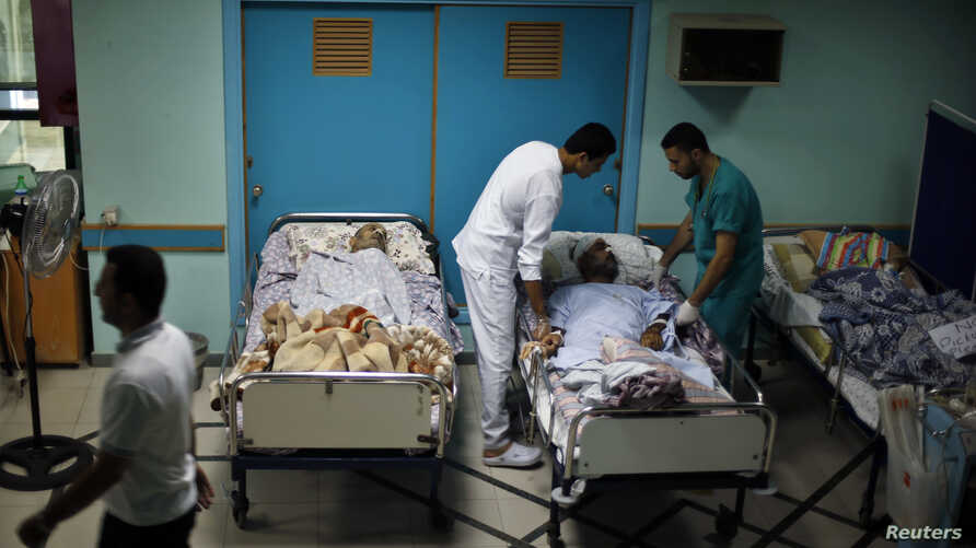 Patients lie in their beds on the ground floor of al-Wafa rehabilitation hospital after being evacuated from the fourth floor, which police said was hit by a tank shell fired by Israeli troops, in the east of Gaza City July 16, 2014.