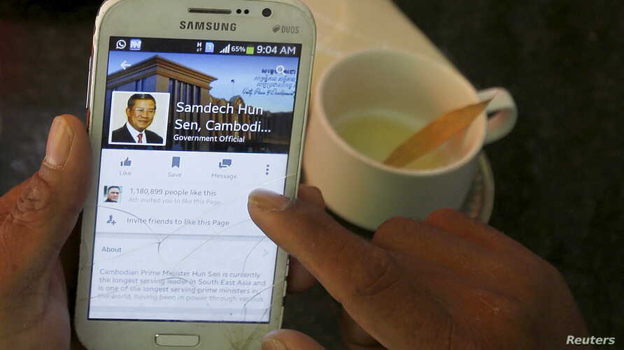 FILE - A person uses a smartphone to look at the Facebook page of Cambodia's Prime Minister Hun Sen during breakfast at a restaurant in central Phnom Penh, Cambodia, Oct. 7, 2015.