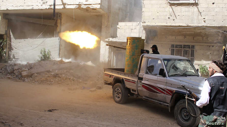 A rebel fighter fires during clashes with Syrian forces in eastern al-Ghouta, near Damascus, April 8, 2014.