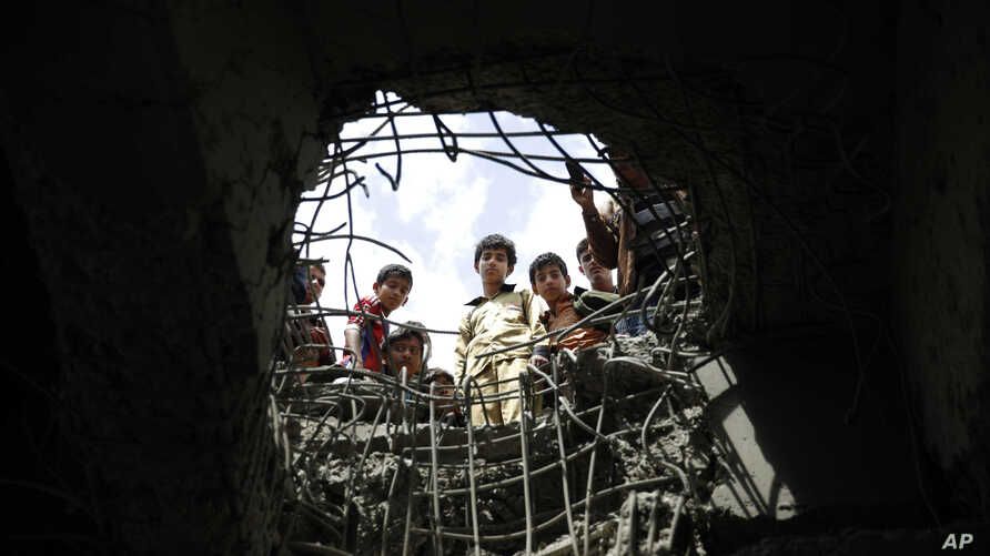 Boys look through a hole made by a Saudi-led airstrike on a bridge in Sanaa, Yemen, March 23, 2016.