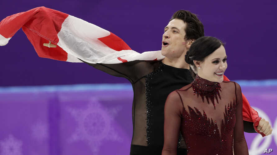 Tessa Virtue and Scott Moir of Canada celebrate during the venue ceremony after winning the gold medal in the ice dance, free dance figure skating final in the Gangneung Ice Arena at the 2018 Winter Olympics in Gangneung, South Korea, Feb. 20, 2018.